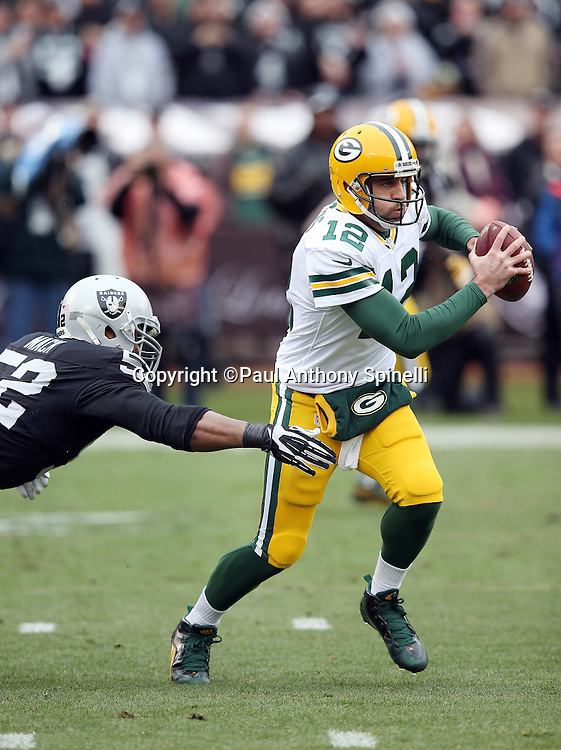 Green Bay Packers quarterback Aaron Rodgers (12) gets sacked by Oakland Raiders defensive end Khalil Mack (52) on a third down play in the first quarter during the 2015 week 15 regular season NFL football game against the Oakland Raiders on Sunday, Dec. 20, 2015 in Oakland, Calif. The Packers won the game 30-20. (©Paul Anthony Spinelli)