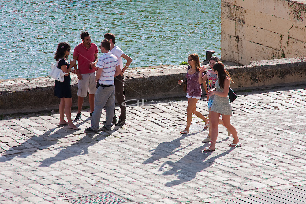 people strolling on the river front in sevilla, spain
