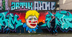 © Licensed to London News Pictures. 11/02/2020. London, UK. A man walks past graffiti depicting Prime minister Boris Johnson as a clown, near Brick Lane in London. Photo credit: Vickie Flores/LNP