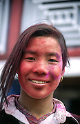 A portrait of a young Nepali girl covered in red and purple dye during the Holi festival in the Nepal Himalaya, April 1995
