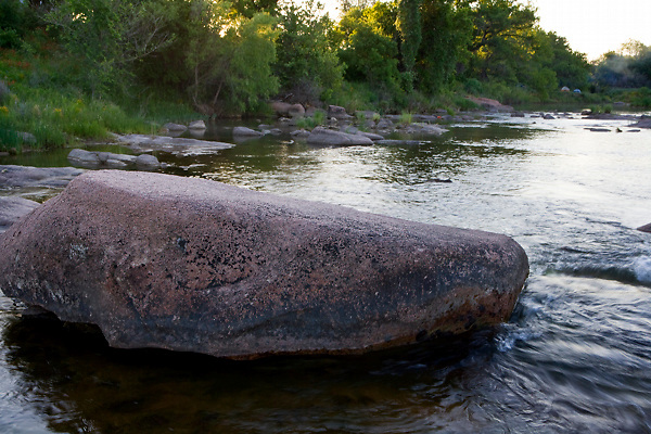 Stock photo of water flowing around a boulder in the Llano River in the Texas Hill Country