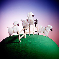 Sheep jumping over a fence in a dream world.