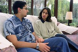 Single mother sitting on sofa talking with teenage son,