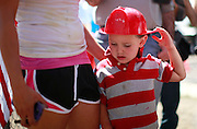 Casen Beyea, 3, wearing a toy fireman's helmet pauses at a memorial in Prescott, Arizona to firefighters killed in the nearby wildfire July 2, 2013.   An elite squad of 19 Arizona firemen was  killed in the worst U.S. wildland firefighting tragedy in 80 years apparently outflanked and engulfed by wind-whipped flames in seconds, before some could scramble into cocoon-like personal shelters on June 30, 2013. REUTERS/Rick Wilking (UNITED STATES)