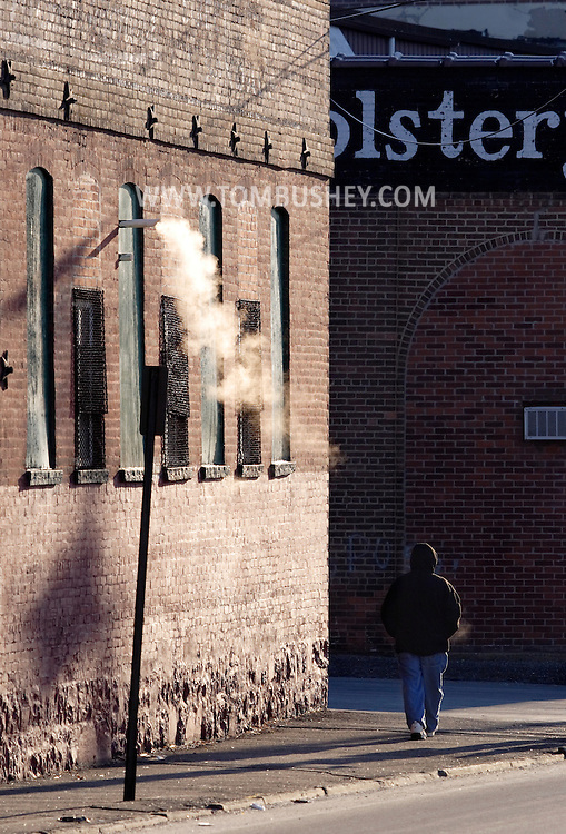 Middletown, N.Y. - A man walks down the street on a cold winter morning on Jan. 26. 2007, as a pipe vents steam from a factory building.