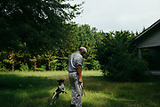 "MERIDIAN, MS – AUGUST 3, 2018: Clayton George, 57, passes near the old farm house where his father was raised. The home, which is now flanked on all sides by pine trees, reminds George of his family's heritage on the land stretching as far back as 1926. Now a resident of Tennessee, George makes the four hour drive south every two weeks to check in on the 400 acre tract, and visit his father who still lives there.<br /> <br /> In 1987, George and a friend walked in rows planting the family's first batch of Loblolly pine, where soybeans, wheat and cattle once covered the family's 400 acres.  The shift to timber was largely prompted by the Conservation Reserve Program, a popular new farm subsidy in the 1980s that encouraged farmers to reforest depleted land by paying them for every acre of trees planted. Since 1926, the George family had made a good living from their eastern Mississippi farm, but the decline of soybeans and other crops eventually led George to consider growing trees instead – a crop that landowners throughout the south believed would bring in easy money. Thirty years later, however, the same landowners are now facing unexpected financial hardship. Stumpage prices have been on a steady decline – as much as 45% since 2007 – and landowners are rethinking timber as a worthwhile investment. """"We figured we''d plant trees and come back and harvest it in 30 years, and in the meantime go into town to make a living doing something else,"" George said. As co-owner of the family acreage with three other family members, George always considered himself the most nostalgic Now, as he patiently awaits for right time to harvest a 30 year investment, even he considers the future of the land uncertain. CREDIT: Bob Miller for The Wall Street Journal<br /> TIMBER_AL"