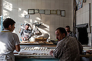 Dough moves from proofing barrel to oven via an assembly line of workers in a firin in Sanliurfa province.