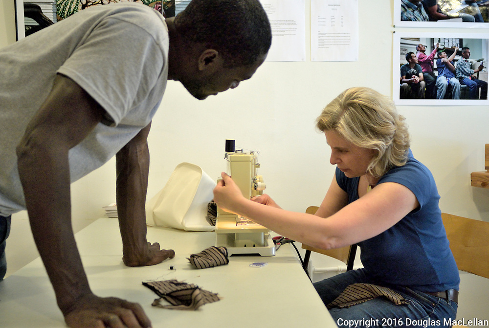 Canada, Windsor, 2016. Sew What Sewing Club, a workers' cooperative intitiated by Mireille Coral. She helps James with a sewing machine threading jam.