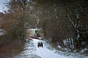 Land Rover in country lane in frosty wintry landscape in The Cotswolds, Oxfordshire, UK