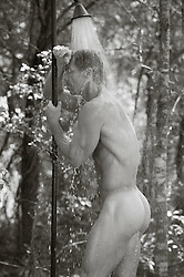 naked man in an outdoor shower in the woods