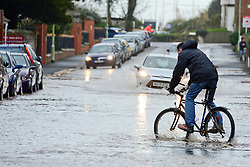 © Licensed to London News Pictures. 03/02/2014. Exmouth, UK. A man ride a bike through floodwater.  Seawater floods the seafront in Exmouth Devon.The water breached defences and flooded Morton Road, St Andrews Roads, Victoria Road and some of the other surrounding streets. Police closed the road to vehicles. Officials were seen delivering sandbags to the local residents. . Photo credit : Russ Nolan/LNP