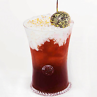 Iced coffee cocktail with gold leaf flecked cherry .