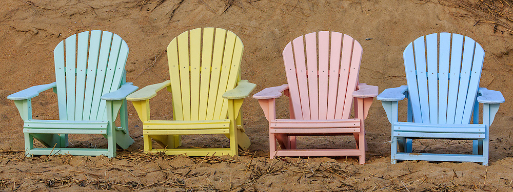 Adirondack chairs lined up against the due in Duck North Carolina Outer Banks.