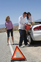 Man and two young women refuelling car on road