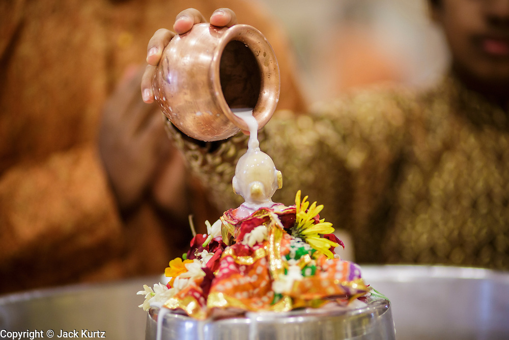10 AUGUST 2012 - PHOENIX, AZ:   People make an offering to a diety during the celebration of Janmashtami at Ekta Mandir, a Hindu temple in central Phoenix. Janmashtami is the Hindu holy day that celebrates the birth of Lord Krishna. Hindu communities around the world celebrate the holy day. In Arizona, most of the Hindu temples in the Phoenix area have special celebrations of the day.  PHOTO BY JACK KURTZ