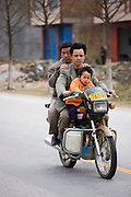 Men and child on a motorbike in Guilin, China. China has a one child family planning policy to reduce population.
