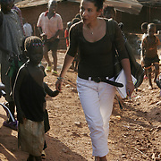 Journalist Mariane Pearl walks through a slum area called the Acholi Quarters where many Acholi people live on the outskirts of Kampala. Dr.Julian Atim, is an Acholi, which is the largest group from Northern Uganda where conflict has raged for the past decade. Historically, the Acholi have been discriminated against by the people in power.