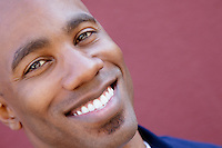 Tilt portrait of a happy African American man over colored background