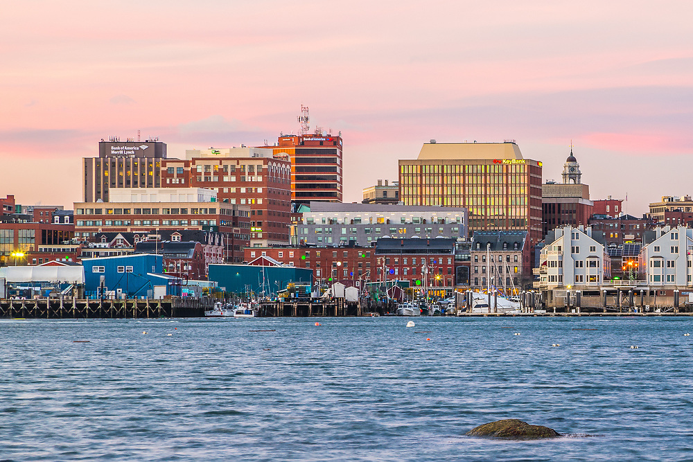 The financial district of Portland Maine stands above and behind the bustling waterfront. You can see Bank of America, Merrill Lynch, TD Bank, Bank of America, Key Bank, City Hall, Hyatt Place, Union Wharf, Chandler Wharf, Widgery Wharf, among many others.