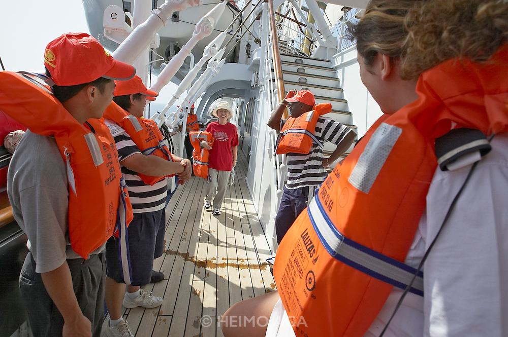 Compulsory safety drill aboard Royal Clipper. Japanese painter Kuriko Shigeta arriving late.