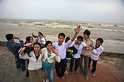 Youngsters having fun on a rainy day at Nam O Beach. A typhoon out at sea makes the waves go high.