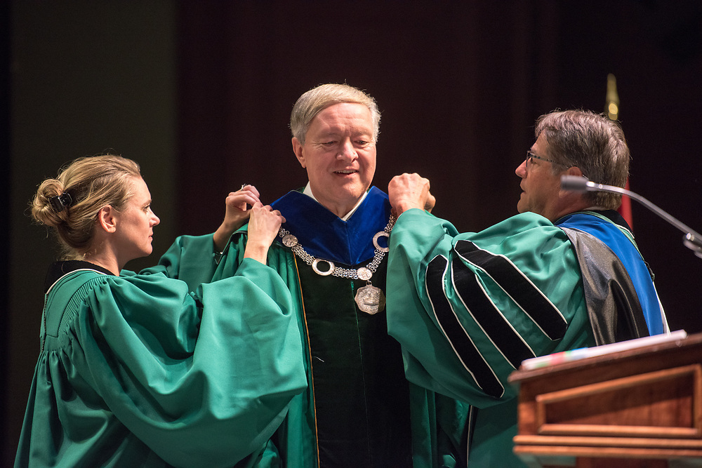 Board of Trustees members Janetta King (left) and David Scholl (right) place the Seal of Office around Dr. Nellis' neck during the ceremony