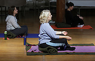 Middletown, New York - Women meditate at the end of a yoga class led by Maria Blon of Create Your Wellness at the First Presbyterian Church on April 21, 2011.