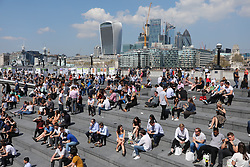© Licensed to London News Pictures. 20/04/2018. London, UK. People on their lunch breaks enjoy the sun in The Scoop by Tower Bridge in London as record April temperatures continue in the capital. Photo credit: Rob Pinney/LNP