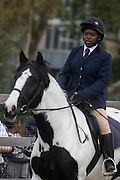A young girl horse rider parades around the equestrian ring while Queen Elizabeth makes a brief visit to the Ebony Horse Club at Loughborough Junction, Brixton, London. Accompanied by the Duchess of Cornwall, Her Majesty watched an equestrian demonstration in one of the most disadvantaged inner city neighbourhoods in the country where there is a historic legacy of under-achievement in schools, high rates of teenage pregnancy and negative stereotypes of young people, gang violence and drug related crime.