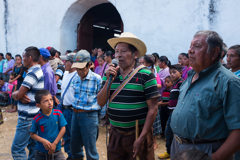 Community elder Cornelio Tec, 79, speaks as locals from Pinares gather before Cahabon's community consultation on extractive projects. In Cahabon, the Oxec hydro-electric projects have begun construction without a proper consultation, an issue that has caused severe divisions among the local population. Out of a population of 70,000 in Cahabon, 26,526 voted against the extractive projects while 11 voted in favor. The consultation was not sanctioned by official authorities. Since 2005, over 90 consultation processes have been carried out in indigenous territories in Guatemalan. These are considered a preventive measure in the struggle to protect indigenous territories and their cultures from unwanted industrial projects. Pinares, Cahabon, Alta Verapaz, Guatemala. August 27, 2017.