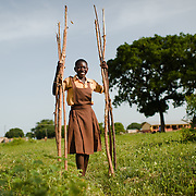 Hawulatu carrying pieces of wood to build a fence at her school in the Upper West region of Ghana on 28 May 2014.