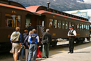 USA, Alaska, Skagway, A conductor watches as tourists board the White Pass & Yukon Route railroad on a sunny day in downtown Skagway.