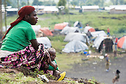 A woman and her child sit on a hill overlooking the Kibati IDP camp on the outskirts of Goma, Eastern Democratic Republic of Congo on Friday December 12, 2008