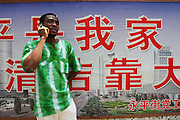 1 August 2007 - Guangzhou, China - Assiongbon Kankoe, 28, from Ghana chats on his mobile phone. By some estimates over 10,000 Africans from many different nations live and pass through Guangzhou which has overtaken Hong Kong as the new hub for African businessmen looking to cut out the middle man. Some come for a few weeks, others years. These African traders, most of whom come from West African nations like Ghana, Togo and Nigeria, profit by purchasing cheap goods direct from Chinese factories and then sending them back to their home countries where they can be sold at higher prices. Photo Credit: Luke Duggleby
