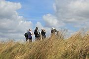 Group of birdwatchers using binoculars at Boyton RSPB nature reserve, Suffolk, England,UK