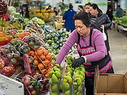 29 FEBRUARY 2020 - ST. PAUL, MINNESOTA: A woman sets up her vegetable stand in the produce market in the Hmong Village. Thousands of Hmong people, originally from the mountains of central Laos, settled in the Twin Cities in the late 1970s and early 1980s. Most were refugees displaced by the American war in Southeast Asia. According to the 2010 U.S. Census, there are now 66,000 ethnic Hmong in the Minneapolis-St. Paul area, making it the largest urban Hmong population in the world. Hmong Village, the largest retail and restaurant complex that serves the Hmong community, has more than 250 shops and 17 restaurants.   PHOTO BY JACK KURTZ