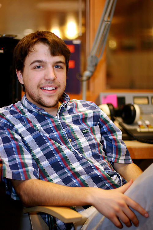 Linn Davis '09 poses for a portrait in his home away from home, the KDIC radio station on Monday.