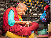 31 JULY 2015 - KATHMANDU, NEPAL:  A Tibetan Buddhist devotee at Bodhnath Stupa. Bodhnath Stupa in the Boudha section of Kathmandu is one of the most revered and oldest Buddhist stupas in Nepal. The area has emerged as the center of the Tibetan refugee community in Kathmandu. On full moon nights thousands of Nepali and Tibetan Buddhists come to the stupa and participate in processions around the stupa. The stupa was heavily damaged in the earthquake of 25 April 2015 and people are no longer allowed to climb on the stupa, now they walk around the base and pray with butter lamps.  PHOTO BY JACK KURTZ