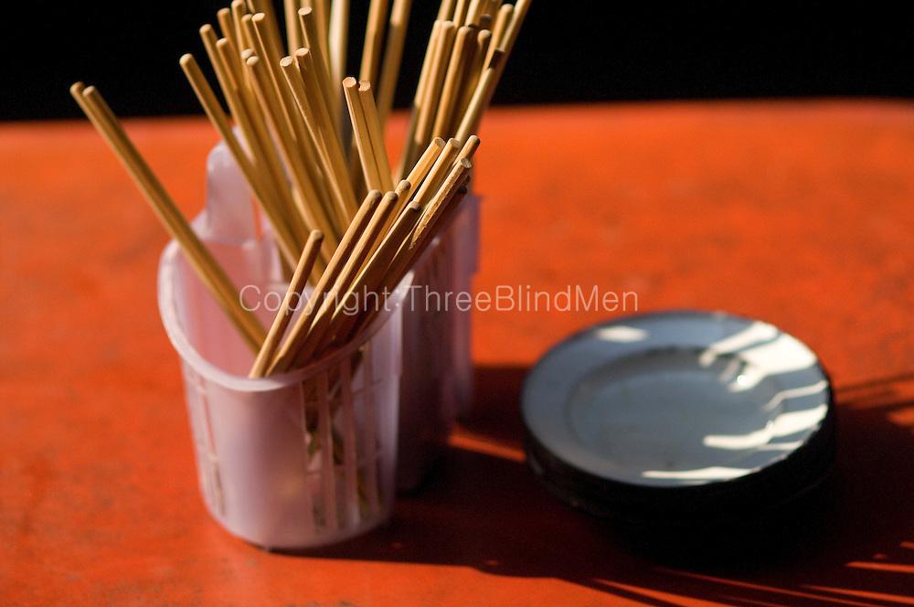 Chopsticks and plates at street food stall in Chinatown, Bangkok,