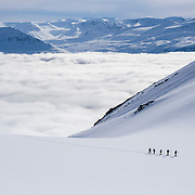 A group skins above a sea of clouds with Bergmenn Mountain Guides, North Iceland