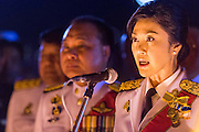 YINGLUCK SHINAWATRA (center) the Prime Minister of Thailand, reads a proclamation honoring the King at the celebration of the birthday of the King in Bangkok. Thais observed the 86th birthday of Bhumibol Adulyadej, the King of Thailand, their revered King on Thursday. They held candlelight services throughout the country. The political protests that have gripped Bangkok were on hold for the day, although protestors did hold their own observances of the holiday. Thousands of people attended the government celebration of the day on Sanam Luang, the large public space next to the Grand Palace in Bangkok.