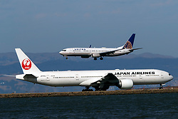 Boeing 737-924(ER) (N68836) operated by United Airlines landing past Boeing 777-346(ER) (JA742J) operated by Japan Airlines, San Francisco International Airport (KSFO), San Francisco, California, United States of America