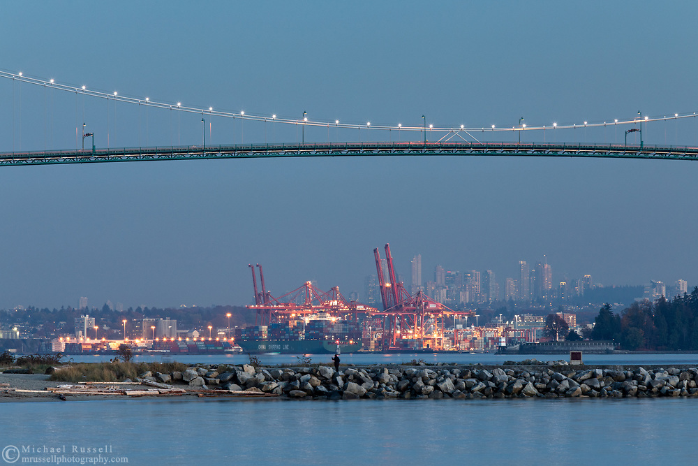 The Port of Vancouver, Lions Gate Bridge, and Ambleside Park in the early evening. Photographed from Ambleside Fishing Pier betwen John Lawson and Ambleside Parks along the shoreline in West Vancouver, British Columbia, Canada. Background towers are in the city of  Burnaby.