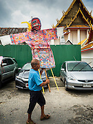 11 SEPTEMBER 2015 - BANGKOK, THAILAND:  A man carries an offering into Wat Kalayanamit before a food distribution for poor members of the community at Wat Kalayanamit in the Thonburi section of Bangkok. Food distribution is a common way of making merit in Chinese Buddhist temples. Wat Kalayanamit, a Thai Theravada temple, was founded by a Chinese-Thai family in the 1820s and observes both Thai and Chinese Buddhist traditions. The food distribution was not related to the temple's efforts to evict people living on the temple grounds, but many of the people at the food distribution live in the houses the temple plans to raze.   PHOTO BY JACK KURTZ