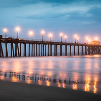 Panorama picture of Huntington Beach Pier and dramatic blue storm clouds at night. Huntington Beach California is a popular Orange County coastal city in the Western United States.