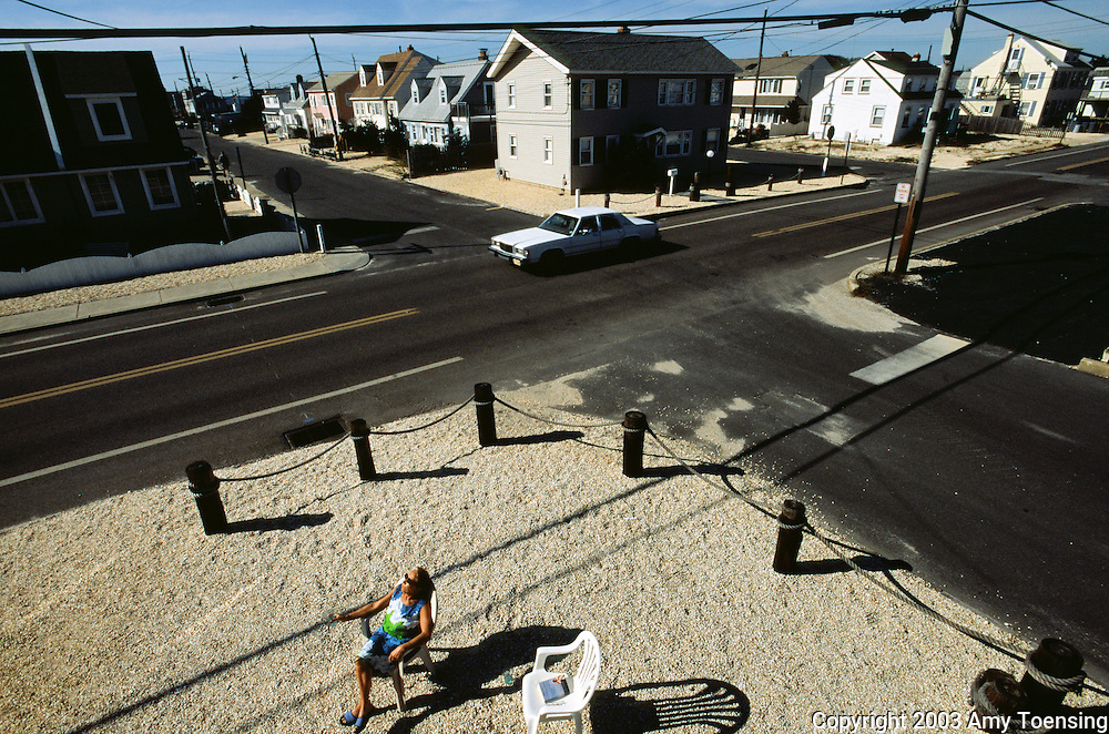 LONG BEACH ISLAND, NJ - SEPTEMBER 09: A woman takes in the sun outside her beach rental home September 9, 2003 on Long Beach Island, New Jersey. The Jersey Shore, a 127 mile stretch of coastline known for its variety of beaches, boardwalks, small towns, natural beauty and summer crowds, has been a popular summer destination for over a century. (Photo By Amy Toensing)