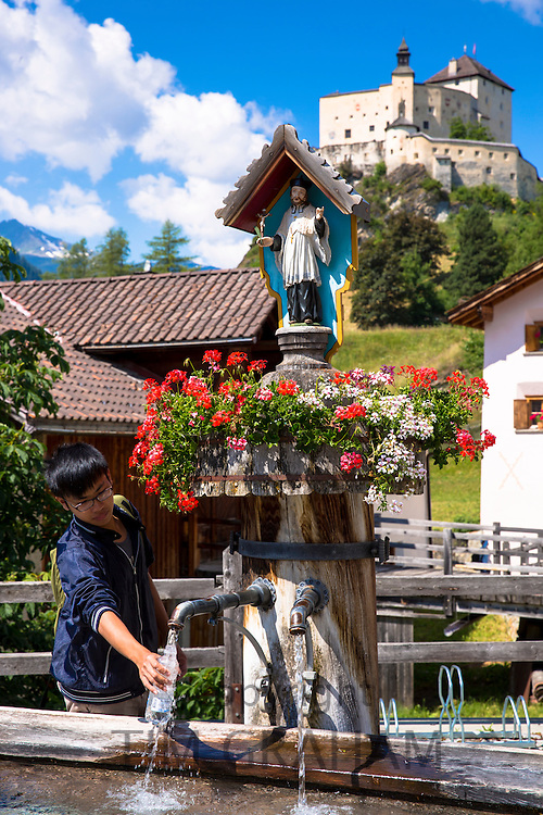Tourist filling bottle from water fountain on a visit toTarasp Castle in the Lower Engadine Valley, Switzerland