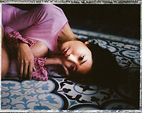 A portrait of a young woman on a tile floor in Vietnam.