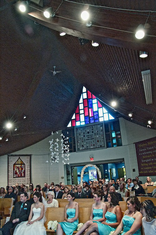 Brantford's (Ontario, Canada) Fairview United Church has a unique design, full of intriguing angles. Spotlights illuminate the interior while the foyer has an open space including a comfortable lounge area. Here, we can see Katie and Brad sitting in the bottom left as they listen to the sermon on their wedding day. <br /> <br /> To view Katie and Brad's complete Wedding Gallery Collection, visit the Client Area and log-in. You'll be able to view all images as a slideshow, order prints and more.<br /> <br /> &copy; Images of a Promise by Dean Oros Photo + Design