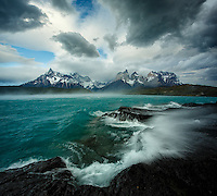 An unforgettable morning in Patagonia's Torres del Paine National Park. Gale force winds transform the calm turquoise colored waters of Lake Pehoe into a raging sea, blowing away crashing waves and literally lifting the water off the lake surface, all of this against the unforgettable mountain backdrop of los Cuernos del Paine!